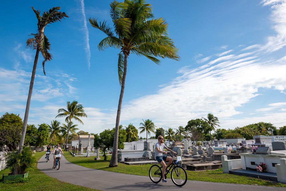 Key West, Florida, USA - January 17, 2015: Visitors ride rental bicycles through the historic Key West Cemetery, established in 1847 after a hurricane washed bodies out from their previous location.