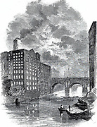 Manchester at night: Blackfriars Bridge and a view of cotton mills from the river Irwell showing the mill windows lit up as a night shift was at work . Engraving c1850.