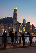 Five people stand at the Kowloon waterfront at dusk, looking across Victoria Harbour to the Central district of Hong Kong Island. (August 2019)