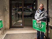 26 JANUARY 2020 - DES MOINES, IOWA: A man holding an Amy Klobuchar yard sign stands in the door and listens to Sen. Klobuchar speak during a campaign event in Des Moines Sunday evening. Sen. Klobuchar campaigned to support her candidacy for the US Presidency Sunday in central Iowa during the one day break from the impeachment trial of President Trump. She is trying to capitalize on her recent uptick in national polls. Iowa holds the first selection event of the presidential election cycle. The Iowa Caucuses are Feb. 3, 2020.       PHOTO BY JACK KURTZ