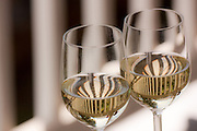 Two glasses of white wine reflecting ballusters of a hand railing