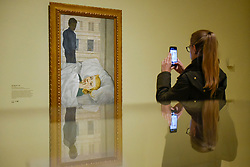 """© Licensed to London News Pictures. 23/10/2019. LONDON, UK. A visitor views """"Hotel Bedroom"""", 1954, by Lucien Freud. Preview of """"Lucian Freud: The Self-portraits"""" at the Royal Academy of Arts in Piccadilly.  56 works on display chart Freud's artistic development over almost seven decades on canvas and paper in a show which runs 27 October to 26 January 2020.  Photo credit: Stephen Chung/LNP"""
