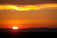 The sun rises above a distant ridge into a red sky to start a new day.