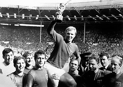 Bobby Moore holds aloft the World Cup as his teammates celebrate around him