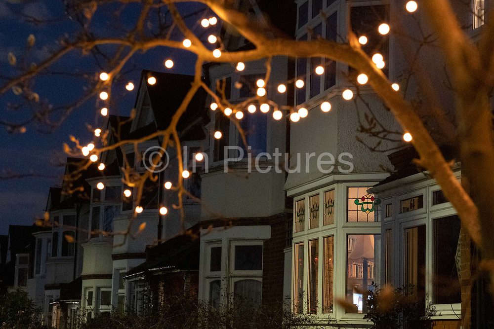 With Christmas fairy lights still hanging in garden trees, house lights in a residential home shines through the windows of a bay window in Herne Hill, south London, on 26th February 2021, in London, England.
