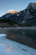 Hope Mountain alpenglow is reflected in the ice of a frozen Silver Lake at Silver Lake Provincial Park near Hope, British Columbia, Canada
