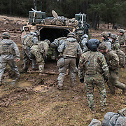 U.S. Army Sgt. 1st Class Marcia McNeill,Charlie Company, 2nd Battalion, 3rd Combat Aviation Brigade, 3rd Infantry Division, calmy surveys the scene as litter teams from 1st Battalion, 8th Cavalry, 1st Cavalry Division unload casualties from an armored troop carrier, Feb. 1, 2020, during Combined Resolve XIII at Hohenfels Training Area.  (U.S. Army photo by Sgt. 1st Class Garrick W. Morgenweck)