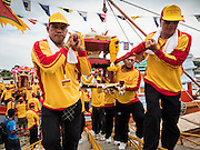"""23 JUNE 2015 - MAHACHAI, SAMUT SAKHON, THAILAND: Men carry offerings for City Pillar off a fishing boat during the procession in Mahachai. The Chaopho Lak Mueang Procession (City Pillar Shrine Procession) is a religious festival that takes place in June in front of city hall in Mahachai. The """"Chaopho Lak Mueang"""" is  placed on a fishing boat and taken across the Tha Chin River from Talat Maha Chai to Tha Chalom in the area of Wat Suwannaram and then paraded through the community before returning to the temple in Mahachai.  PHOTO BY JACK KURTZ"""