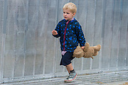 A child and his companion patrol teh pit wall - The 2017 Latitude Festival, Henham Park. Suffolk 16 July 2017
