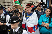 Pro Trump protesters react to angry opposition and are protected by police outside a pub during protests against the state visit of US President Donald Trump on 4th June 2019 in London, United Kingdom. Organisers Together Against Trump which is a collaboration between the Stop Trump Coalition and Stand Up To Trump, have organised a carnival of resistance, a national demonstration to protest against President Trump's policies and politics during his official UK visit.