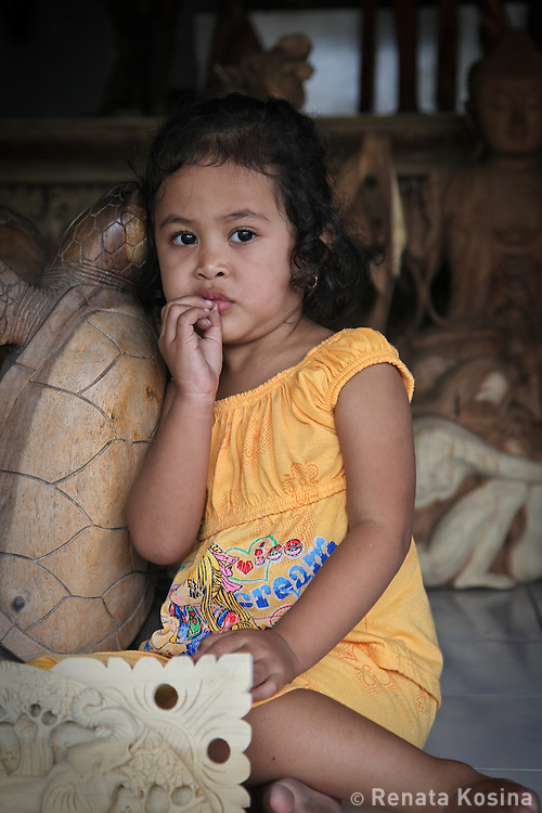 A young Balinese girl resting at her father's woodworking shop in village of Mas. Many similar shops line the main street as many individual Balinese villages specialize in specific types of craft like woodworking, painting, jewelry, etc. Their work is often produced for export.