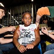 """Nederland Rotterdam 8 oktober 2008 Foto: David Rozing ..Vaccinatiedag AHOY in teken van overgewicht en opvoeden.Vandaag werden in AHOY Rotterdam zo'n 4.000 kinderen uit het Noorden van Rotterdam gevaccineerd tegen de infectieziekten difterie, tetanus en polio (DTP) en bof, mazelen en rode Hond (BMR). Na de vaccinaties kunnen ouders gebruik maken van advies van een diëtist en van een pedagoog..Twee keer per jaar houdt de GGD Rotterdam-Rijnmond een grote vaccinatiedag voor 9-jarigen. Op 8 oktober krijgen ongeveer 4000 kinderen een vaccinatie tegen ernstige infectieziekten als difterie, tetanus en polio (DTP) en/of bof, mazelen en rode Hond (BMR). Enkele 9-jarigen krijgen ook nog een Hibvaccinatie (tegen Haemophilus influenzae type b). Er worden ook zo'n 500 kinderen gevaccineerd die zich pas in Rotterdam hebben gevestigd. Voor deze kinderen moet soms het buitenlandse schema worden ingepast in het Nederlandse Rijksvaccinatieprogramma (RVP).""""??Meten, wegen en opvoedingsadvies??De GGD grijpt de vaccinatiedag aan om méér te doen dan de bescherming tegen infectieziekten. De kinderen kunnen na de twee prikken meteen doorlopen voor het bepalen van hun lengte en gewicht. Er zijn diëtisten aanwezig, zodat ouders en kinderen zich kunnen laten adviseren over gezonde voeding en beweging. En als ouders vragen hebben over de opvoeding van hun kind kunnen zij deze ter plekke stellen aan één van de veertien aanwezige pedagogen. ??Activiteiten voor kinderen over ontbijten??Er zijn allerlei activiteiten te doen in het teken van ontbijten. Een diëtist maakt samen met kinderen gezonde ontbijtjes. Er is een muzikale theatervoorstelling over het belang van ontbijten. Op een groot scherm wordt een filmpje vertoond en met een ontbijtquiz zijn drie fietsen te winnen. Alle kinderen krijgen een attentie mee naar huis.??Actieprogramma Voeding en beweging??De GGD houdt deze voedings- en bewegingsactiviteiten in het kader van het actieprogramma Voeding en Beweging. Met dit programma wil de gemeent"""