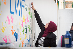 17 February 2020, Zarqa, Jordan: Incentive-Based Volunteer Esraa from Jordan paints her handmark on the wall of the Lutheran World Federation community centre in Zarqa. Through a variety of activities, the Lutheran World Federation community centre in Zarqa serves to offer psychosocial support and strengthen social cohesion between Syrian, Iraqi and other refugees in Jordan and their host communities.