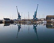 Two large blue industrial cranes reflected  in water of Wet Dock marina, Ipswich, Suffolk, England