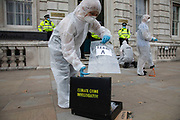 Extinction Rebellion 'crime scene investigators' in white suits and masks put up climate crime scene tape to investigate areas of ecocide and find 'Exhibit A' in a performance outside the Cabinet Office on 7th September 2020 in London, United Kingdom. The 20 investigators were protesting at the UK government's ecocide along the HS2 route. Extinction Rebellion is a climate change group started in 2018 and has gained a huge following of people committed to peaceful protests. These protests are highlighting that the government is not doing enough to avoid catastrophic climate change and to demand the government take radical action to save the planet.