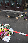 Bullet holes and blood on window panes. Flowers on the street. Cafe Bonne Biere, Rue Fontaine au Roi, near Republique<br />