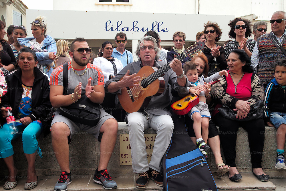 """French and Spanish Gitans play music near the church<br /><br />""""Le Pelerinage des Gitans""""; the French gypsy pilgrimage of Saintes Maries de la Mer, Camargue, France<br /><br />Sainte Sara is an uncannonized saint, who legend says looked after the Christian Saints Marie Jacobe and Marie Salome, cousins of Mary Magdalene, who arrived, it is said, on the shores of the Camargue in a rudderless boat. Saint Sara is the patron saint of gypsies who come from far and wide to see her. There are even paintings of Sara as 'Kali' the black saint in Eastern Europe. Sara may have been the priestess of 'Ra' the sun-god or even servant girl to the Christian saints. No-one really knows.<br /><br />For a few weeks of the year, Roma, Gitan and Manouche gypsies come from all over Europe in May, camping in caravans around Saintes Maries de la Mer. It is a festive time where they play music, dance, party and christen their children. They all go to see Saint Sara in the crypt, kissing or touching her forehead. Many put robes on her shoulders, making her fat for the procession. In the main Gypsy procession of the 24th May, Saint Sara is allowed to leave her crypt, beneath the church, and is carried from the church to the shores of the mediterranean and back again. One day a year she is free from her prison. Hundred's of years ago the Gypsies used not even to be allowed into the church, only into the crypt like Sara...<br /><br />Roma gypsies still suffer oppressive prejudice and racism and are one of the ethnic groups the most persecuted and marginalised across Europe. The festival is one of the times where they celebrate with people of all races, their faith and traditions"""