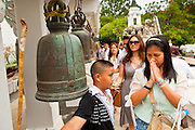 """15 JULY 2011 - PHRA PHUTTHABAT, SARABURI, THAILAND:  People ring holy prayer bells at Wat Phra Phutthabat in Phra Phutthabat, Saraburi, Thailand. The temple is famous for the way it marks the beginning of Vassa, the three-month annual retreat observed by Theravada monks and nuns. The temple is highly revered in Thailand because it houses a footstep of the Buddha. On the first day of Vassa (or Buddhist Lent) people come to the temple to """"make merit"""" and present the monks there with dancing lady ginger flowers, which only bloom in the weeks leading up Vassa. They also present monks with candles and wash their feet. During Vassa, monks and nuns remain inside monasteries and temple grounds, devoting their time to intensive meditation and study. Laypeople support the monastic sangha by bringing food, candles and other offerings to temples. Laypeople also often observe Vassa by giving up something, such as smoking or eating meat. For this reason, westerners sometimes call Vassa the """"Buddhist Lent."""" The tradition of Vassa began during the life of the Buddha. Most of the time, the first Buddhist monks who followed the Buddha did not stay in one place, but walked from village to village to teach. They begged for their food and often slept outdoors, sheltered only by trees. But during India's summer rainy season living as homeless ascetics became difficult. So, groups of monks would find a place to stay together until the rain stopped, forming a temporary community. Wealthy laypeople sometimes sheltered monks on their estates. Eventually a few of these patrons built permanent houses for monks, which amounted to an early form of monastery.    PHOTO BY JACK KURTZ"""