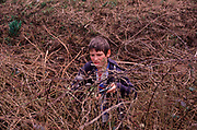 AE2CG8 Young boy cutting brambles in overgrown garden