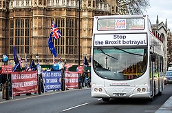 "© Licensed to London News Pictures. 10/12/2018. London, UK. A bus branded with ""Stop the Brexit Betrayal"" passes a group of anti-Brexit demonstrators outside Parliament. Photo credit: Rob Pinney/LNP"