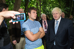 © Licensed to London News Pictures. 30/07/2015. London, UK. The Mayor of London and MP for Uxbridge and South Ruislip Boris Johnson has a photograph taken with an unimpressed looking man during a visit the Wide Horizons Environment Centre in Bexley where he explored their new outdoor learning centre which was built by an 'army of volunteers' on a once derelict site. Photo credit : James Gourley/LNP