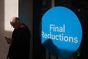 Circular Final Reductions sign outside a City of London shop and coincidental round bald-headed man. A theme of circles and rounded shapes are seen in spring sunlight. The man inspects his smartphone and his shadow is on the background where the lettering is printed and placed in the window of the retailer.