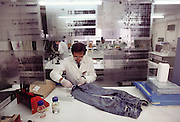 (1992) Forensic use of DNA fingerprints. A scientist taking a sample from a bloodstained pair of jeans. DNA from the sample is then sequenced, providing a DNA fingerprint (such as those seen at the edges of the frame). This may then be compared with DNA from the victim and any suspect. In some cases, this may be used in conjunction with other evidence to positively link a suspect with both the victim and the scene of a crime. Modern amplification techniques allow DNA sequences to be taken from extremely small samples, such as a few spots of blood or a few hair follicles. (Scientist here is J. Bark). MODEL RELEASED