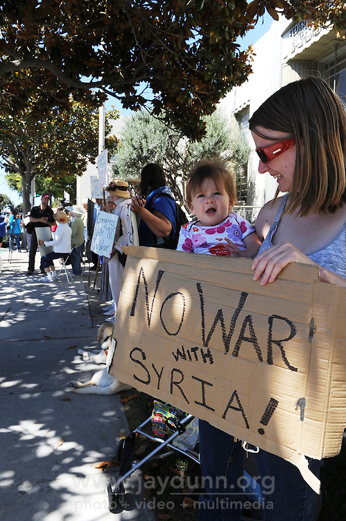 Kristin Steffens and 8 month-old Arkadia participate in Wednesday's protest against war in Syria organized by the Peace Coalition of Monterey County in front of the main post office in Salinas. The demonstration was in support of Congressman Sam Farr's stated antiwar position.
