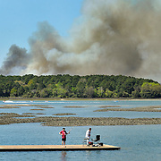 Fishermen lounge at the end of a dock at the Rowing and Sailing Center at Squire Pope Community Park on Hilton Head Island on March 31, 2015.  Portions of Pinckney Island National Wildlife Refuge, seen in the background, are closed Tuesday due to controlled burn activity, according to the U.S. Fish and Wildlife Service. The main trail and all side trails are closed beyond Ibis Pond.