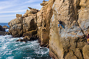 Local rock climber Eric Berghorn climbs a sport route above the ocean in Salt Point State Park, California.