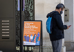 © Licensed to London News Pictures. 06/04/2021. London, UK. Members of the public walk past a rapid Covid-19 test centre at Chelsea Town Hall, South West London as the government announce bi-weekly Covid tests from Friday for everyone in England. Photo credit: Alex Lentati/LNP