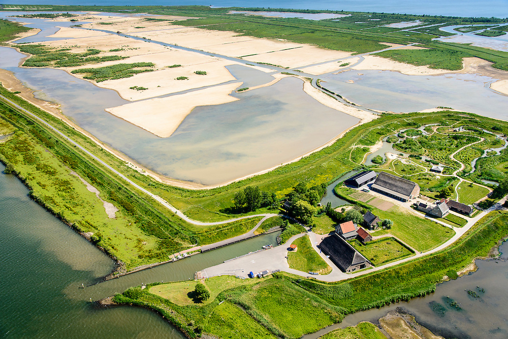 "Nederland, Zuid-Holland, Tiengemeten 10-06-2015; middendeel van het eiland Tiengemeten ter hoogte van de haven en met moeras in wording. <br /> Oorspronkelijk gebruikt voor de akkerbouw maar inmiddels 'teruggegeven aan de natuur', de dijken zijn deels doorgestoken, de laatste boer is in 2006 vertrokken. De 'nieuwe natuur' vormt onderdeel van de Ecologische Hoofdstructuur. <br /> The island Tiengemeten in the Haringvliet, was originally used for agriculture but has now ""been given back to nature"". Large parts have been flooded and the isle is part of the National Ecological Network. The last farmer left in 2006. Current use, among other, care farms and camping.<br /> luchtfoto (toeslag op standard tarieven);<br /> aerial photo (additional fee required);<br /> copyright foto/photo Siebe Swart"