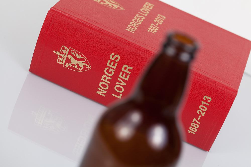 Illustrasjonsfoto på alkoholoven i form av Norges lover og en ølflaske. Fokuset er på boken.