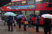 A bus ad for summer beach holidays amid the misery of London in winter, as storm Georgina swept across parts of Britain and in central London, lunchtime office workers were caught out by torrential rain and high winds, on 24th January 2018, in London, England. Pedestrians resorted to leaping across deep puddles at the junction of New Oxford Street and Kingsway at Holborn, the result of overflowing drains.