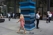 A woman wearing a dress with stripes walks past the artwork entitled Stack Blues by Sean Scully RA, on 25th July 2018, in the City of London. Part of Scully's Landline series of works, Stack Blues is a sculpture borne out of the artist's preoccupation with the horizon.