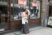 Bride to be on her hen party texting her friends as she waiting outside a suit shop with a sale on, to meet them for her big day out in London, England, United Kingdom.