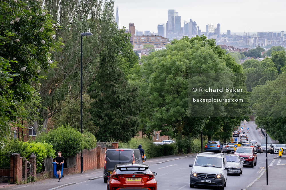With the skyscrapers of the City of London, the capital's financial district, in the distance, a runner climbs uphill and rush-hour traffic builds at the bottom of Sydenham Hill, on 15th June 2021, in south London, England.