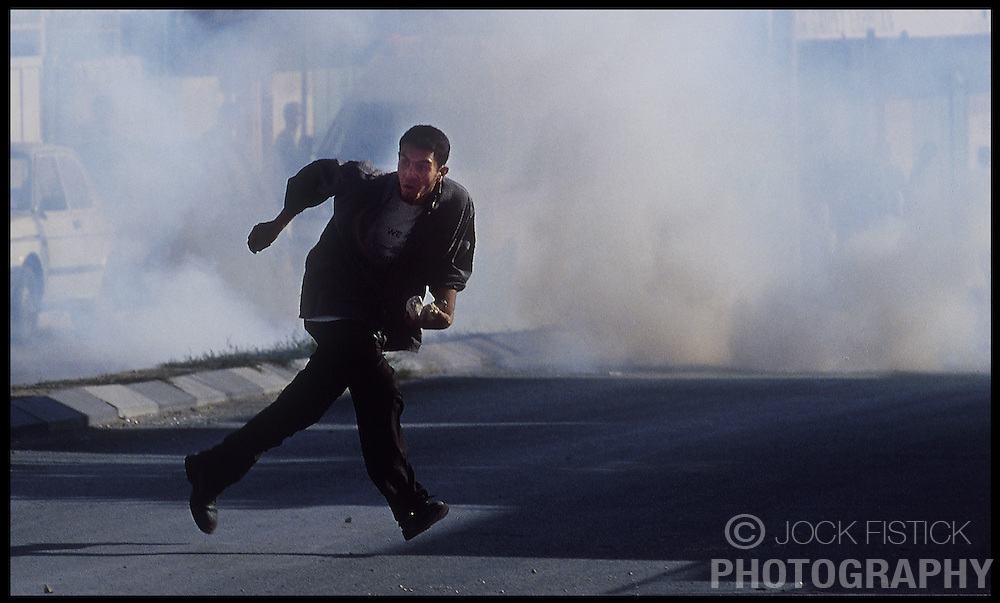 A Palestinian youth runs from tear gas and rubber bullets during a clash with Israeli soldiers near Rachel's Tomb, in the West-bank city of Bethlehem. (Photo © Jock Fistick)