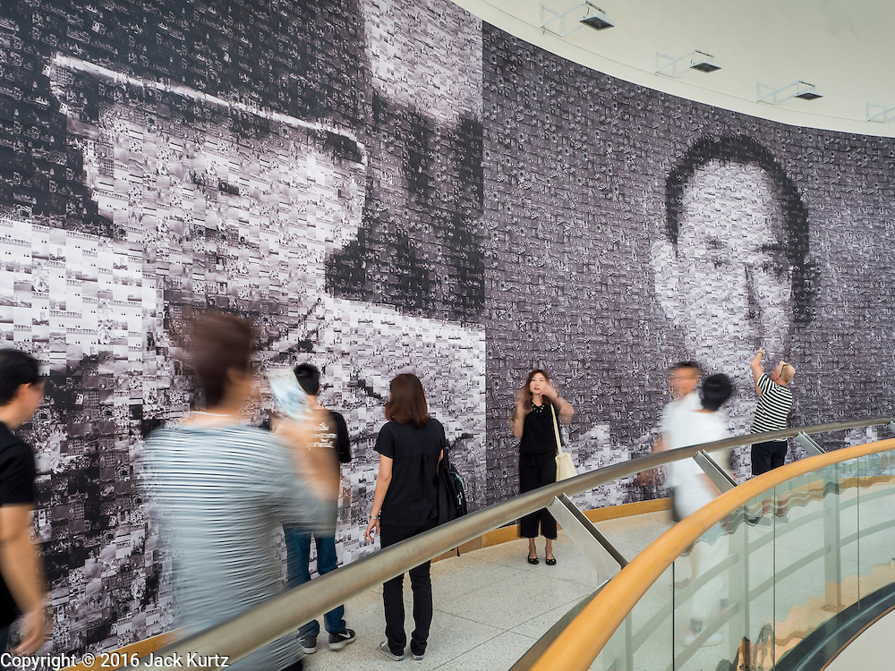 """06 NOVEMBER 2016 - BANGKOK, THAILAND: Thais walk past large mosaic photos of Bhumibol Adulyadej, the late King of Thailand at the Bangkok Art and Culture Centre. The Royal Photographic Society of Thailand with the Bangkok Art and Culture Centre and Thai Beverage Public Company Limited are hosting a photography exhibition to commemorate the late Thai King Bhumibol Adulyadej. The """"In Remembrance of His Majesty King Bhumibol Adulyadej"""" Photography Exhibition is dsiplaying 89 photographs by 89 photographers honoring King Bhumibol Adulyadej's legacy. The King was an avid photographer was usually seen with a camera in his hands. The exhibition will be on display until 27 November 2016 on the Curved Walls on the 3rd - 5th floor, Bangkok Art and Culture Centre.     PHOTO BY JACK KURTZ"""