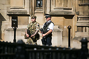 Troops deployed as part of a higher state of emergency in May 24,  London, United Kingdom.  A soldier and police on duty at Westminster Palace.