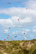 Kite festival of bright color kites in the sky above Rindby Strand beach on Fano Island - Fanoe - South Jutland, Denmark