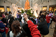 tourists at the Rockefeller Center in NYC  during Christmas time making pictures