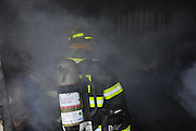 Firefighters with protective equipment enter a smoke filled room