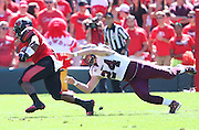 Southern Illinois Salukis linebacker Tyler Williamson (24) dives for Southeast Missouri State Redhawks running back Lennies McFerren (3) in the first quarter. The Southern Illinois University - Carbondale (SIUC) Salukis defeated the host Southeast Missouri State University (SEMO) Redhawks 36-19 in an NCAA football game at Busch Stadium on Saturday September 21, 2013.