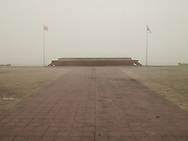 Empty paved place by a foggy day in Vinh, Viet Nam, Asia. Two vietnamese flag fly between a podium