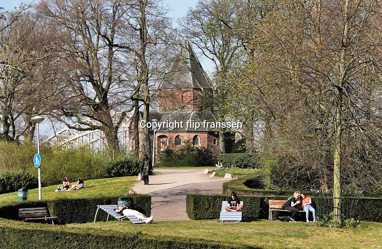 Nederland, Nijmegen, 6-4-2020 De binnenstad van Nijmegen is zo goed als leeg . Het is duidelijk rustiger en stiller in de straten, winkelstraten van het centrum in de stad . Mensen blijven thuis om zo min mogelijk risico te nemen ivm het corona virus . In het valkhofpark, liggen en zitten mensen op afstand van elkaar in de zon .Foto: Flip Franssen