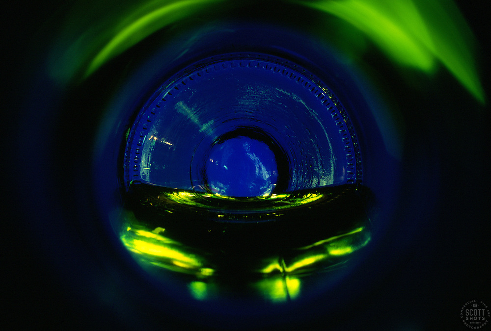 """""""Beauty at the Bottom: White Wine 2""""- This image is a photograph of a wine bottle shot right down the mouth of the bottle. A television provides the main light source."""