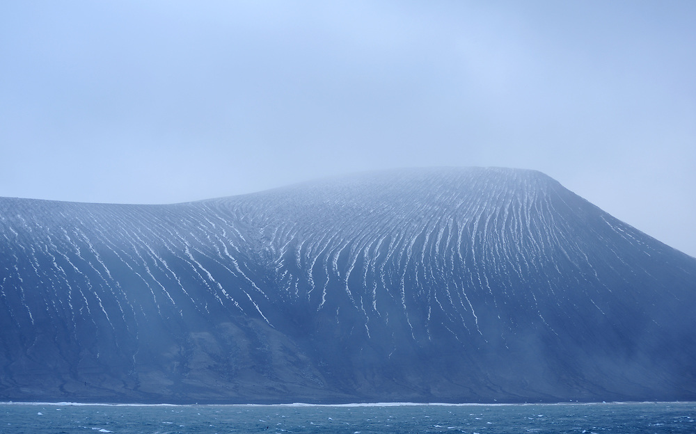 The black volcanic slopes of Saunders Island. The  slopes of black volcanic sand are heavily eroded by rain and wind. Saunders Island, South Sandwich Islands. South Atlantic Ocean. 25Feb16