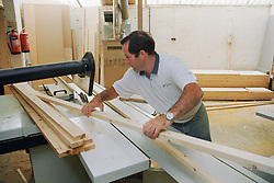 Wood machinist cutting wood to size using dimension saw bench,
