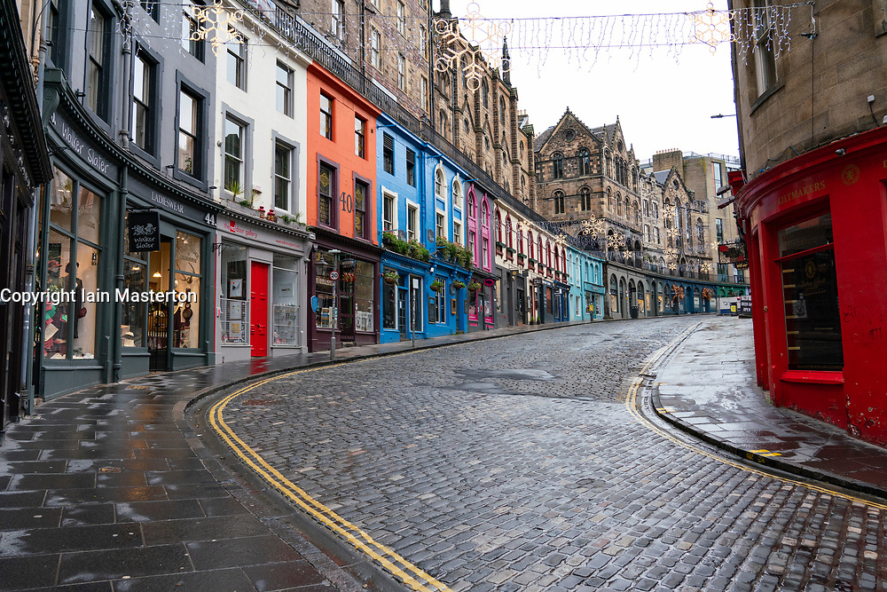 Edinburgh, Scotland, UK. 26 December 2020. Scenes from Edinburgh City Centre on a wet and windy Boxing Day during storm Bella. Today is first day that Scotland is under level 4 lockdown and all non essential shops and businesses are closed. As a result the streets are almost deserted with very few people venturing outside. Pic; Shops on historic Victoria Street is closed and virtually deserted.  Iain Masterton/Alamy Live News